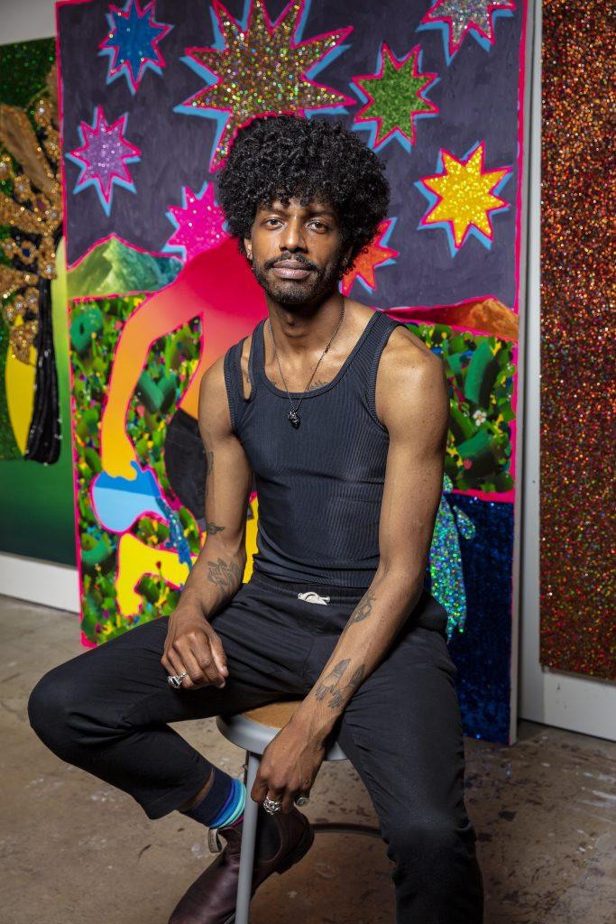 Devan Shimoyama seated with art behind