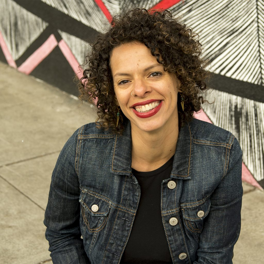 Portrait of a figure in a jean jacket standing in front of a patterned mural.
