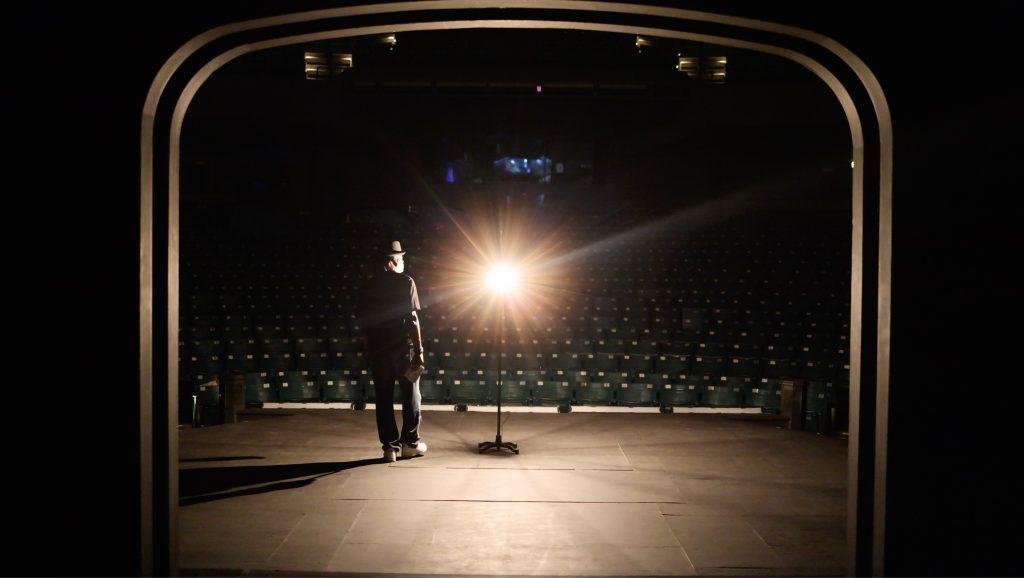 Rising Film still of man on stage